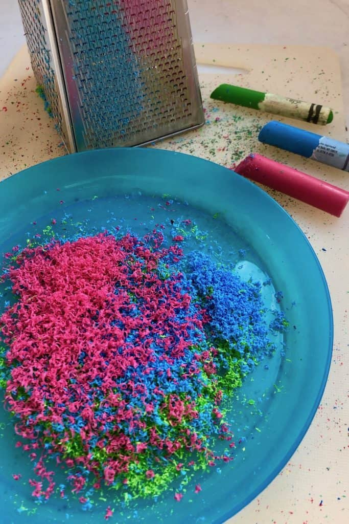 Crayon shavings on a blue plate - pink crayon, blue crayon, and green crayon