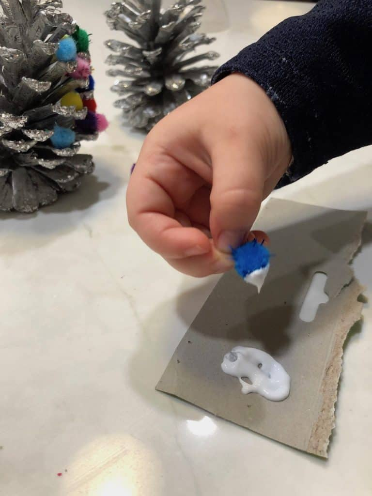 Dip a blue pom pom in glue and put it on the pinecone ornament