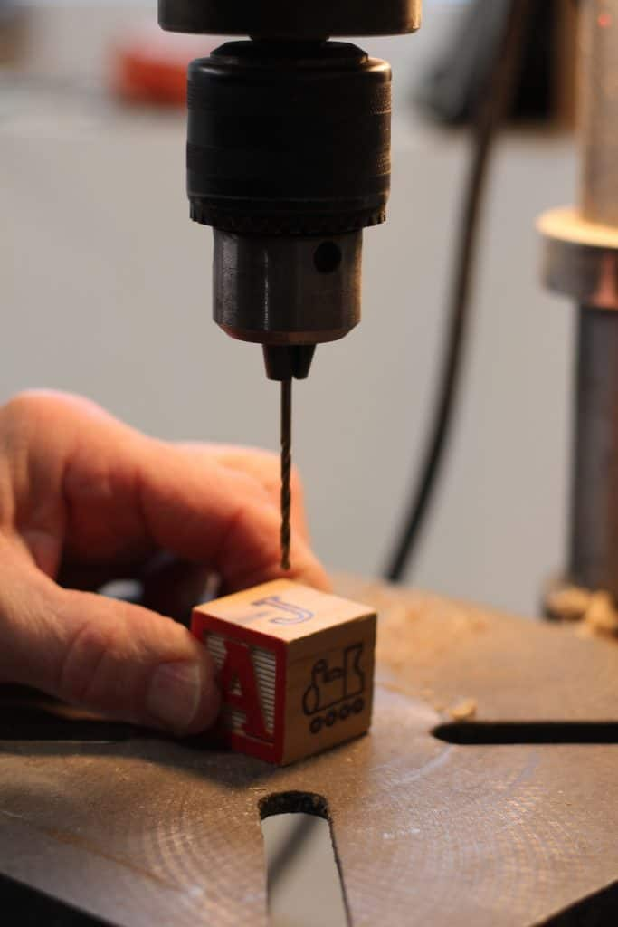 Drilling a hole in an alphabet block to make a Christmas tree ornament