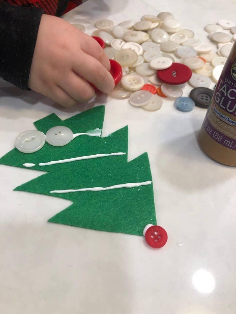 Glueing buttons onto green felt christmas tree