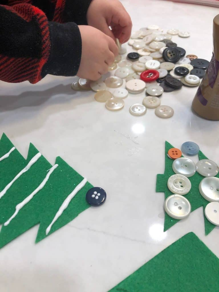 Glueing buttons onto tree ornaments with toddler