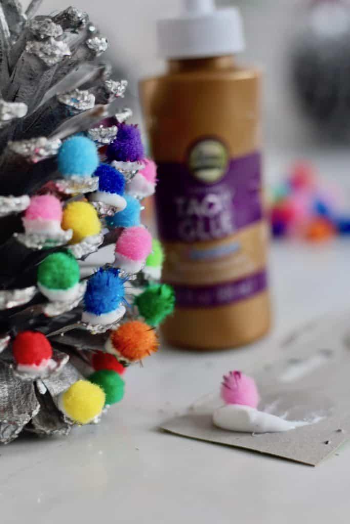 Glueing pom poms onto a pinecone to make a tree ornament for Christmas