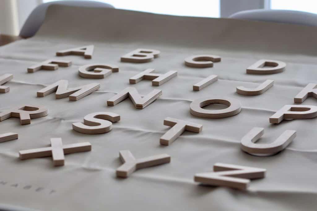 Handmade wooden letters on a Gathre alphabet mat