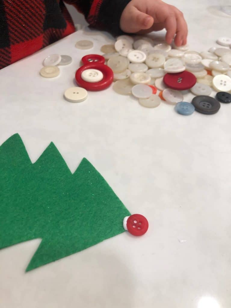 Making preschool Christmas tree ornaments with buttons