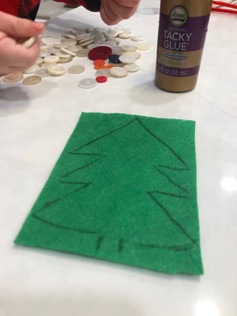 Outline of a Christmas tree drawn on green craft felt with black marker
