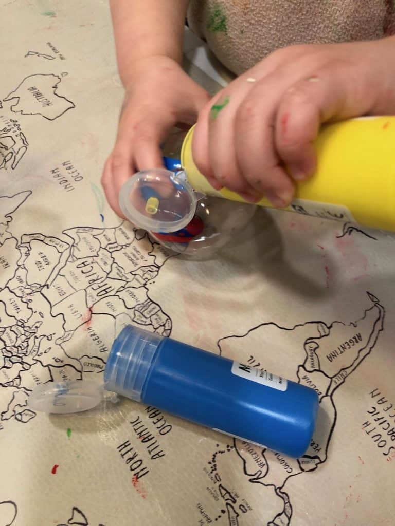 Pouring yellow paint in clear ornament