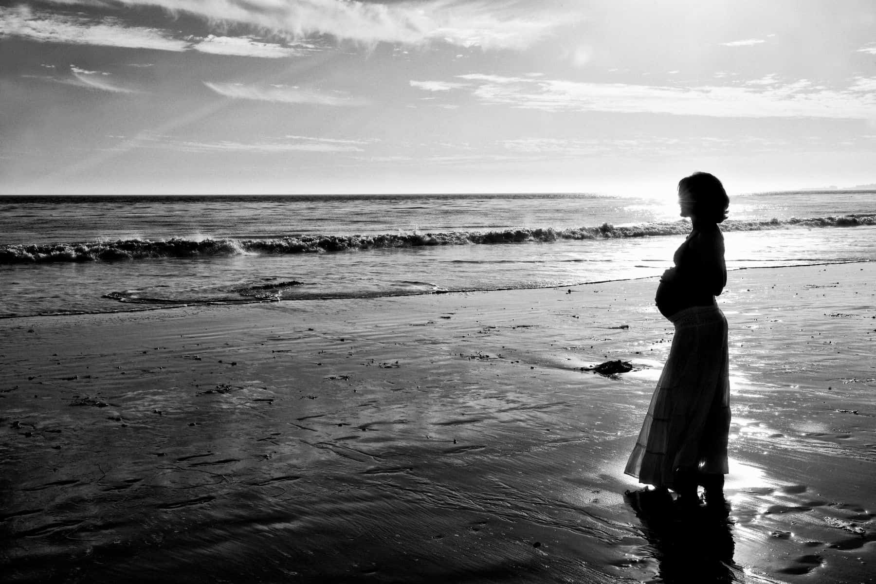 backlit beach silhouette photo - pregnant belly side view