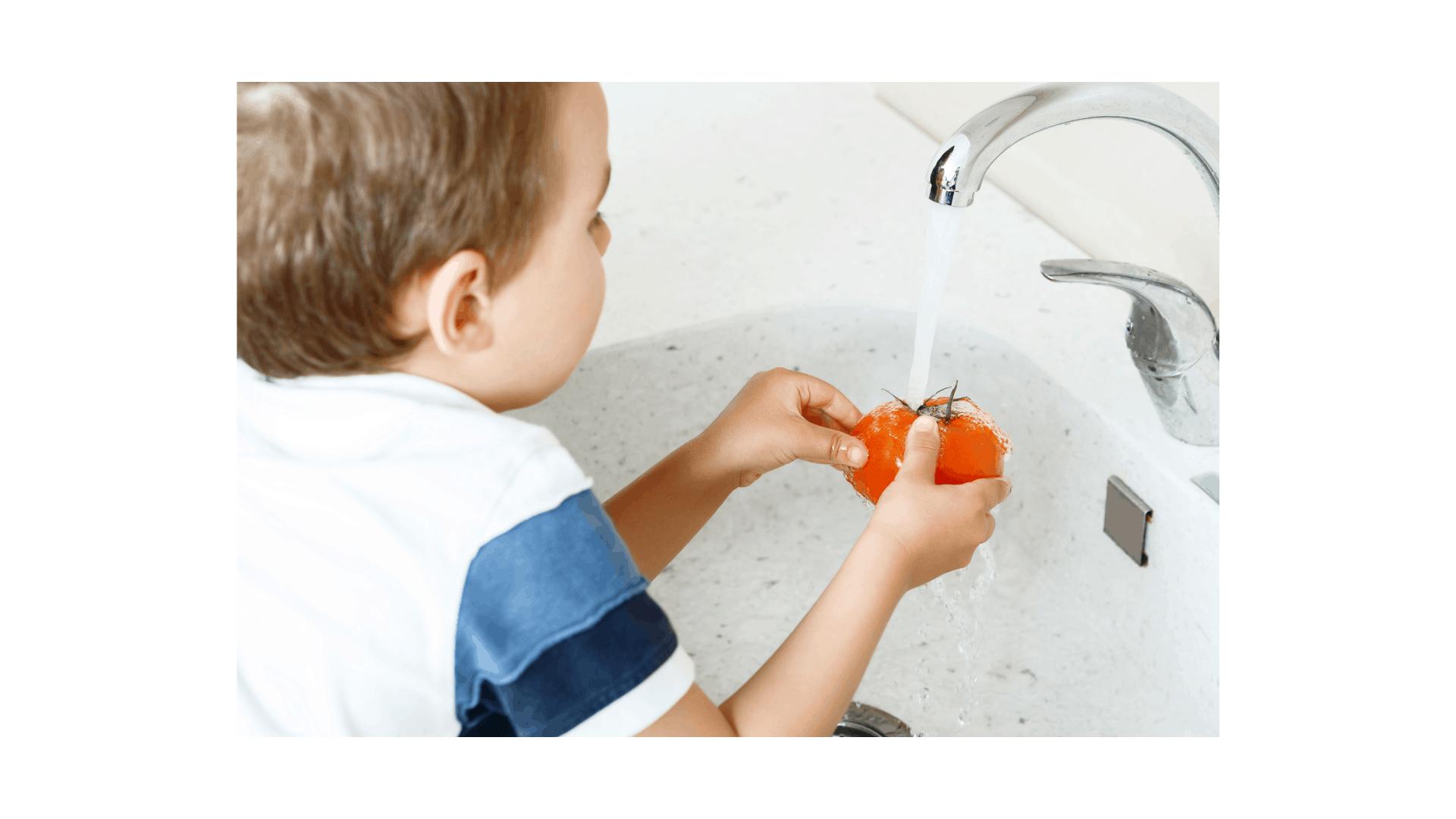 child washing tomato in the kitchen